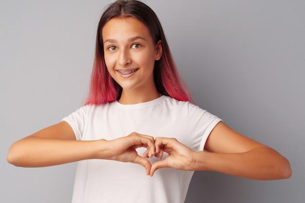 Het jonge tienermeisje wat betreft haar hart met haar overhandigt grijze achtergrond