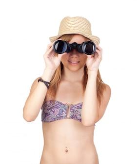 Het jonge toevallige meisje met het letten op van bikini voor een verrekijker solated op witte achtergrond