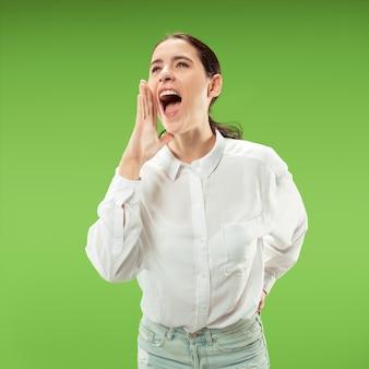 Het jonge toevallige vrouw schreeuwen. roepen. huilende emotionele vrouw die op groene studioachtergrond gilt. vrouwelijke halve lengte portret.