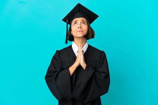 Het jonge universitaire gediplomeerde meisje over geïsoleerde blauwe achtergrond houdt palm samen. persoon vraagt om iets