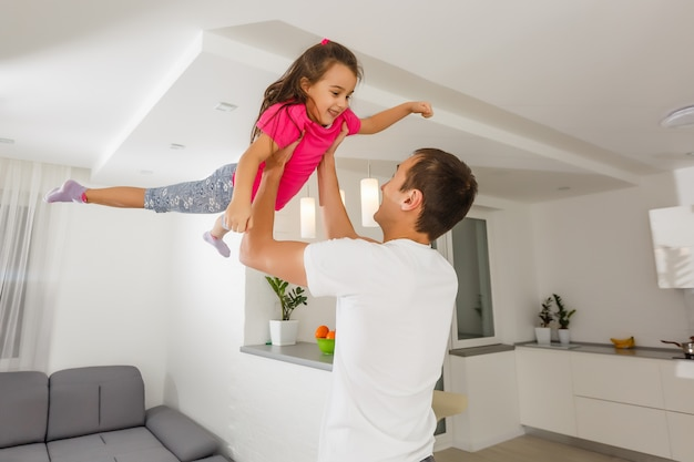 Het jonge vader spelen gek met zijn dochter die haar opheft