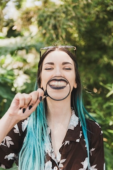Het jonge vergrootglas van de vrouwenholding over de toothy glimlach