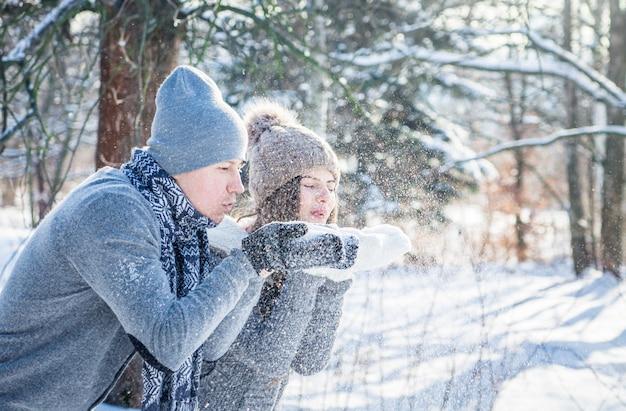 Het jonge verliefde paar blaast sneeuw. verliefde paar dat pret heeft