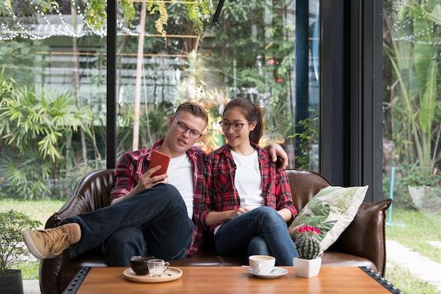 Het jonge verliefde paar glimlacht & bekijkt slimme telefoon. blanke man en aziatische vrouw zitten op de bank thuis in de buurt van venster. vriendje en vriendin daten in café. relatie, minnaar levensstijl