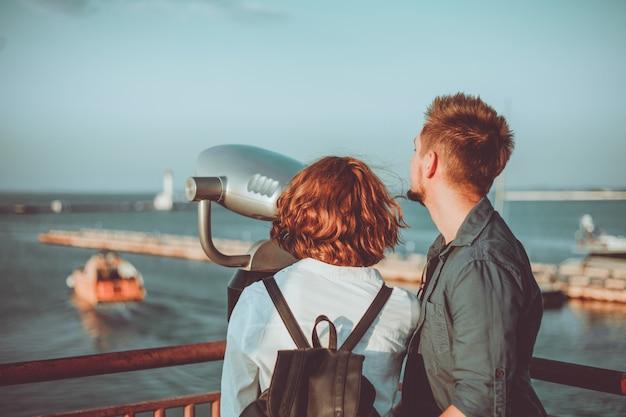 Het jonge verliefde paar kijkt door de verrekijker van de stad op het station van de zee.