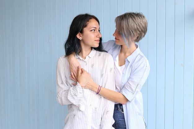Het jonge verliefde paar omhelzen elkaar op blauwe achtergrond