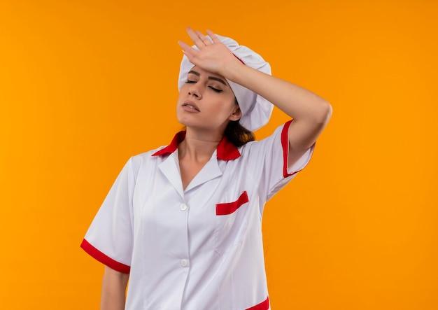 Het jonge vermoeide kaukasische kokmeisje in eenvormige chef-kok legt hand op hoofd met gesloten ogen geïsoleerd op oranje muur met exemplaarruimte