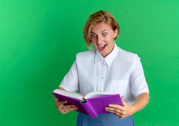 Het jonge verrast blonde russische meisje bekijkt boek dat op groene achtergrond met exemplaarruimte wordt geïsoleerd