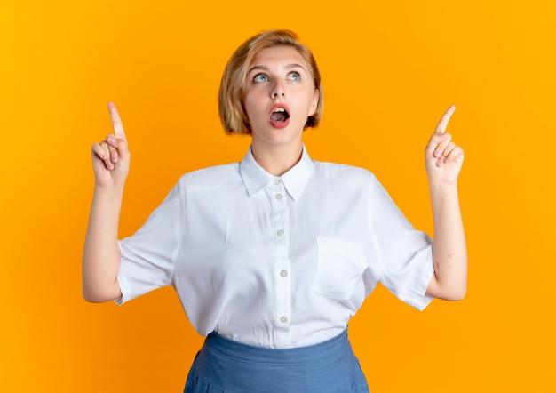 Het jonge verrast blonde russische meisje kijkt en wijst omhoog geïsoleerd op oranje achtergrond met exemplaarruimte
