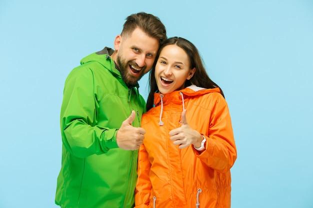 Het jonge verrast couplel poseren in de studio in herfst jassen geïsoleerd op blauw