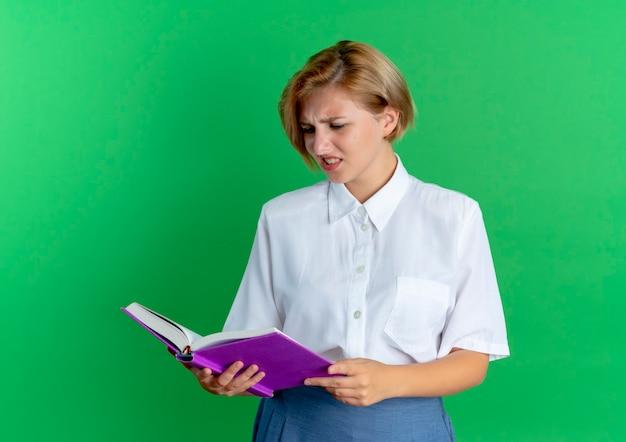 Het jonge verwarde blonde russische meisje houdt en bekijkt boek dat op groene achtergrond met exemplaarruimte wordt geïsoleerd