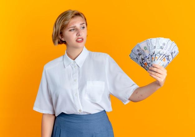 Het jonge verwarde blonde russische meisje houdt en bekijkt geld dat op oranje achtergrond met exemplaarruimte wordt geïsoleerd