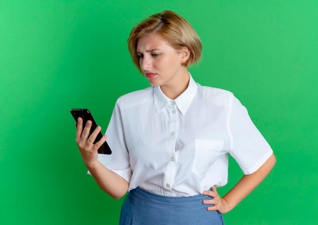 Het jonge verwarde blonde russische meisje houdt en bekijkt telefoon die op groene achtergrond met exemplaarruimte wordt geïsoleerd