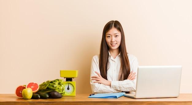 Het jonge voedingsdeskundige chinese vrouw werken met haar laptop glimlachen zeker met gekruiste wapens.