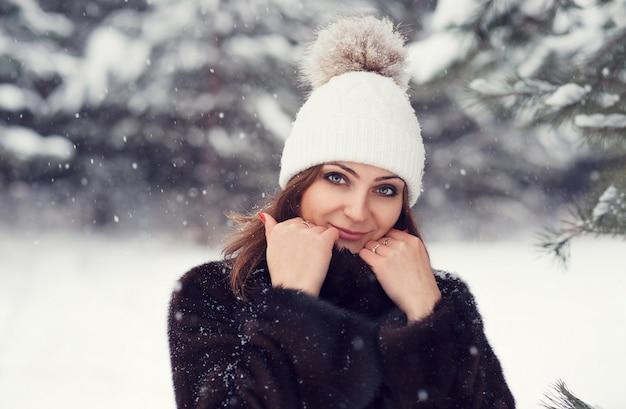 Het jonge vriendschappelijke meisje in een bontjas en de winterhoed glimlacht prachtig in een sneeuwbos.