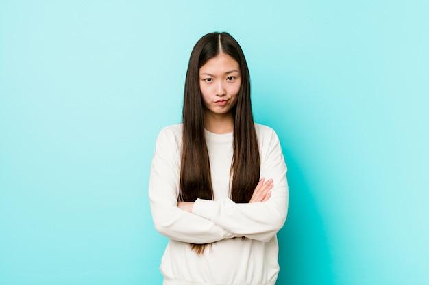 Het jonge vrij chinese vrouw fronsen gezicht in ongenoegen, houdt wapens gevouwen.