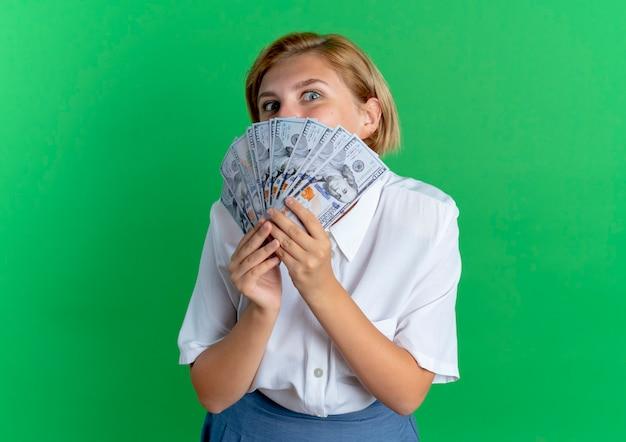 Het jonge vrolijke blonde russische meisje houdt en kijkt over geld dat op groene achtergrond met exemplaarruimte wordt geïsoleerd