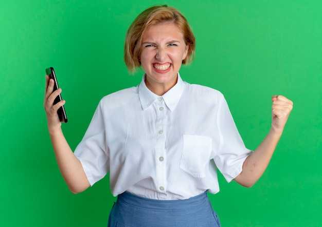 Het jonge vrolijke blonde russische meisje houdt telefoon met opgeheven vuist die op groene achtergrond met exemplaarruimte wordt geïsoleerd
