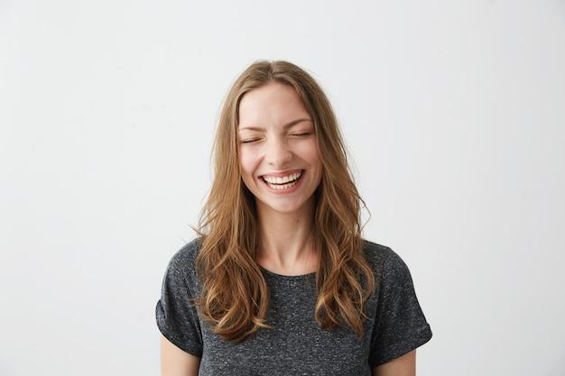 Het jonge vrolijke gelukkige meisje glimlachen die met gesloten ogen lachen.