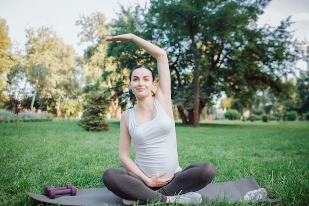 Het jonge vrolijke zwangere vrouw uitrekken zich buiten in park. ze houdt een hand omhoog en een andere op haar buik. model ziet er recht uit en glimlacht. ze zit op yogamaatje.