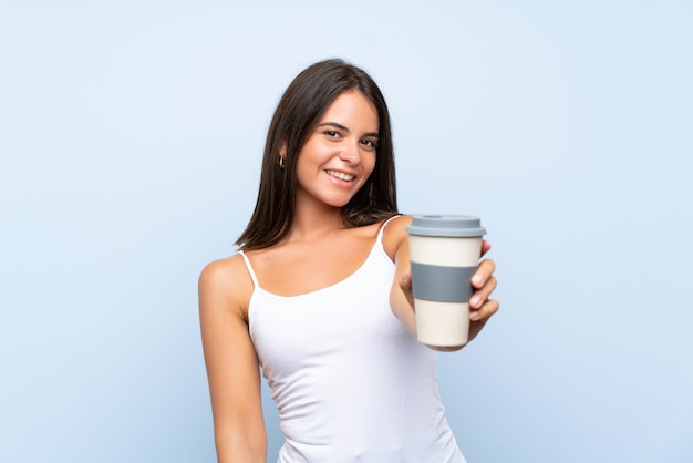 Het jonge vrouw houden haalt koffie over geïsoleerde blauwe muur weg