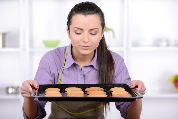 Het jonge vrouw koken in de keuken die een huis bakt.