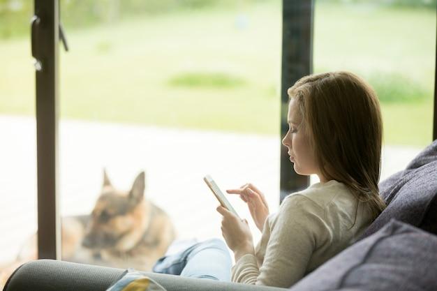 Het jonge vrouw ontspannen op bank die smartphone apps binnen huis gebruiken