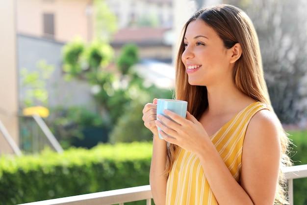 Het jonge vrouw ontspannen op de mok thee van de balkonholding