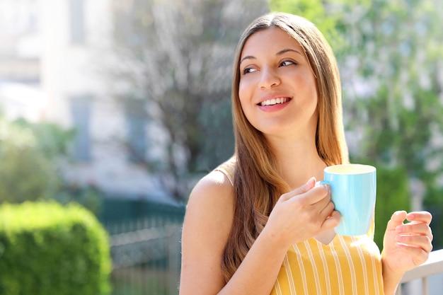 Het jonge vrouw ontspannen op de mok van de balkonholding cappuccino of thee thuis in de ochtend