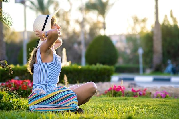 Het jonge vrouw ontspannen op groen grasgazon in de zomerpark.
