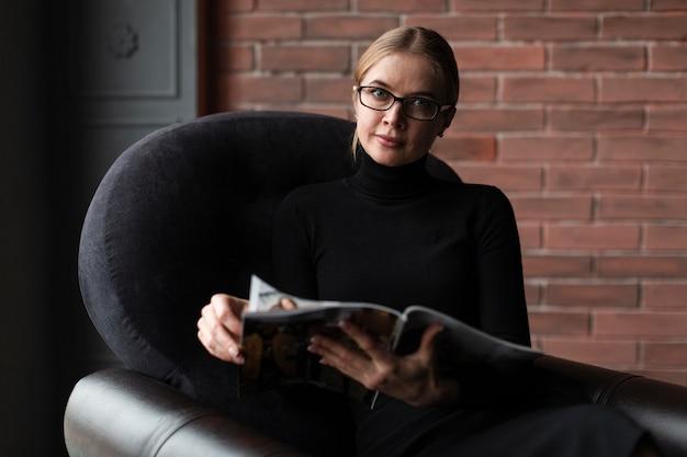 Het jonge vrouw ontspannen op laag met tijdschrift