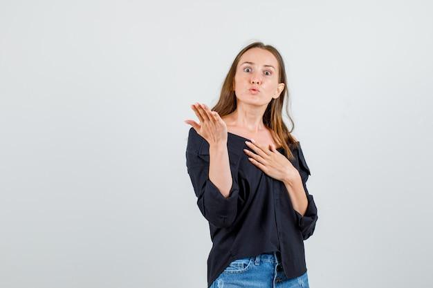Het jonge vrouw opheffen dient overhemd, borrels in en kijkt boos. vooraanzicht.