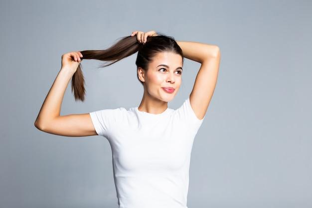 Het jonge vrouw raken en speelt met haar haar dat op wit wordt geïsoleerd