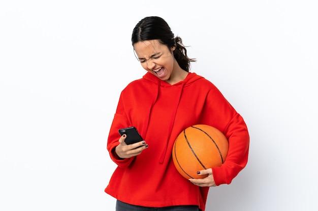Het jonge vrouw speelbasketbal over geïsoleerd wit met telefoon in overwinningspositie