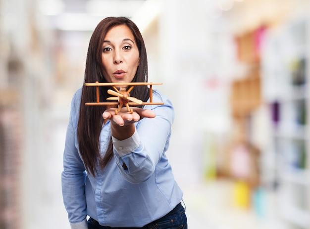 Het jonge vrouw spelen met een houten tweedekker