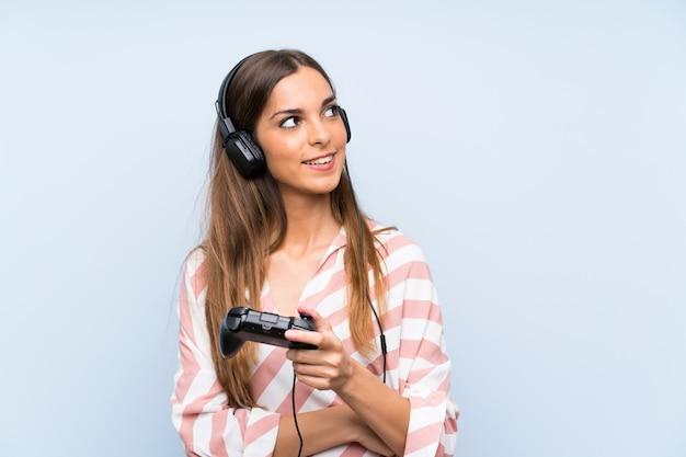 Het jonge vrouw spelen met een videospelletjecontrolemechanisme over geïsoleerde blauwe muur die omhoog terwijl het glimlachen kijkt