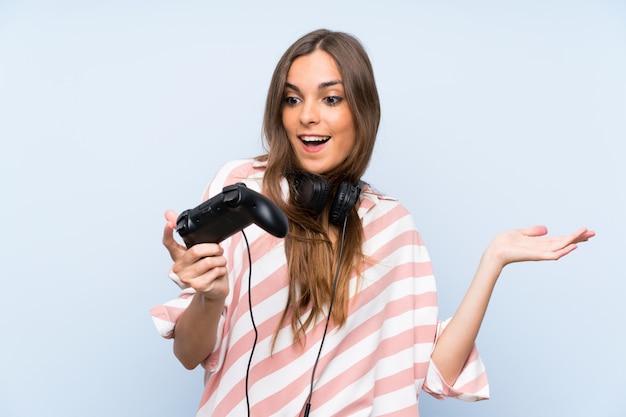 Het jonge vrouw spelen met een videospelletjecontrolemechanisme over geïsoleerde blauwe muur