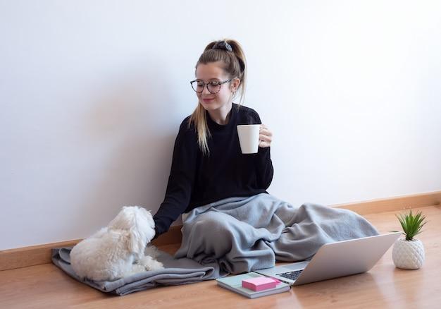 Het jonge vrouw spelen met haar hond en thuis het drinken van koffie