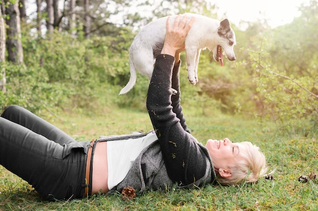 Het jonge vrouw spelen met haar hond in openlucht