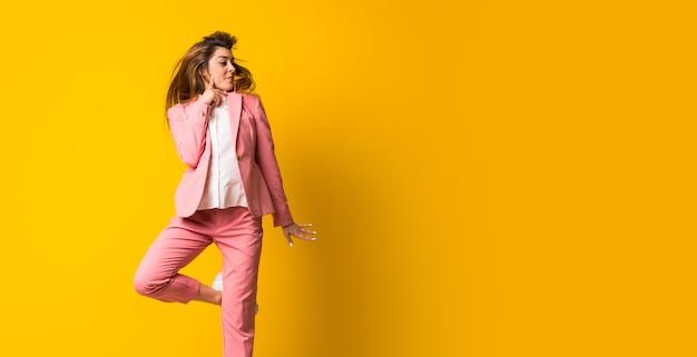 Het jonge vrouw springen geïsoleerd op gele muur