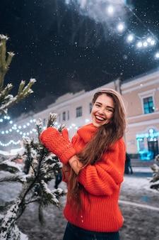 Het jonge vrouw stellen dichtbij de kerstboom op de straat