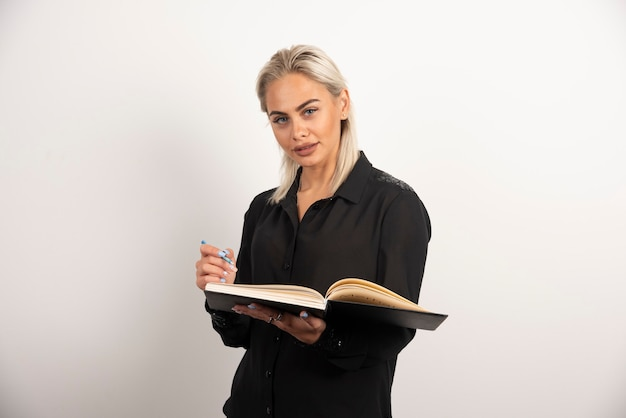 Het jonge vrouw stellen met een kop en een klembord op witte achtergrond. hoge kwaliteit foto