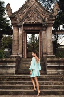 Het jonge vrouw stellen naast oude khmer-ruïnes in kambodja