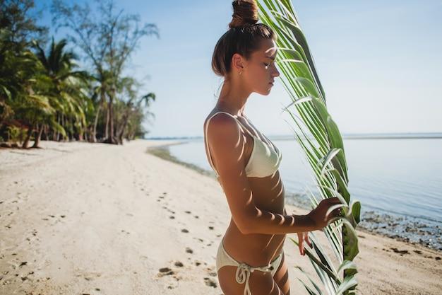 Het jonge vrouw stellen op zandstrand onder palmblad