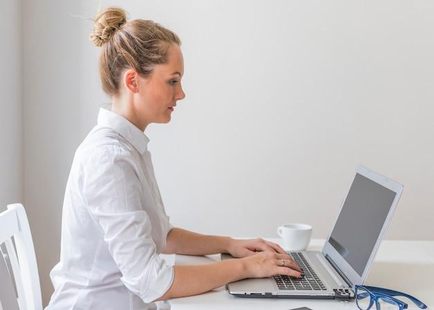 Het jonge vrouw typen op laptop met kop en oogglazen op lijst