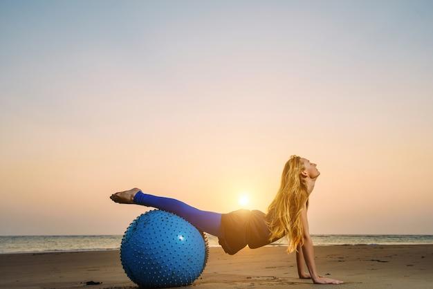 Het jonge vrouw uitrekken zich bij de opleiding van bal tegen zonsondergang over overzees