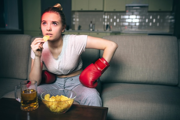 Het jonge vrouwenhorloge in dozen doen op tv bij nacht.