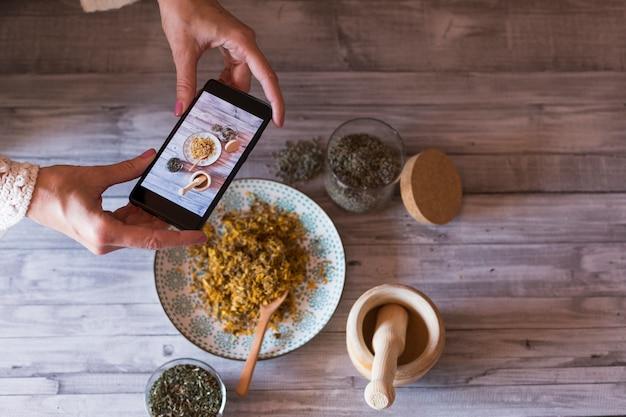 Het jonge vrouwenvoedsel blogger neemt foto voor blog, foto van een houten mortier, kom met gele kurkuma, lavendel en gezonde natuurlijke ingrediënten. selectieve aandacht, close-up. dag