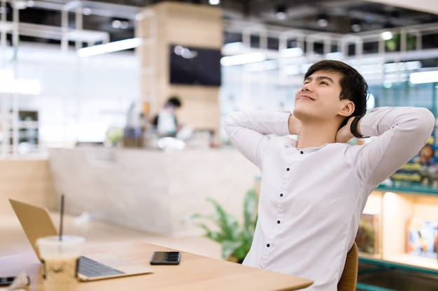 Het jonge zakenman ontspannen bij zijn bureau in co-working ruimte
