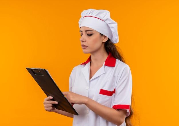 Het jonge zekere kaukasisch kokmeisje in eenvormige chef-kok houdt en bekijkt klembord dat op oranje muur met exemplaarruimte wordt geïsoleerd